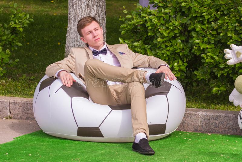 Um grupo de jovens que graduam-se da escola no uniforme elegante senta-se em uma poltrona na forma de uma bola de futebol no símb foto de stock royalty free