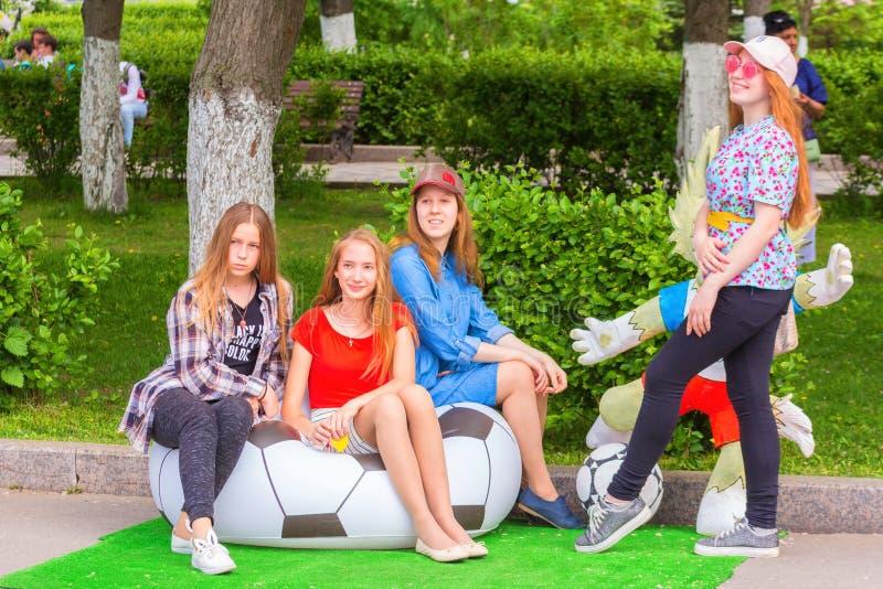 : um grupo de jovens que graduam-se da escola no uniforme elegante senta-se em uma poltrona na forma de uma bola de futebol no sy fotos de stock