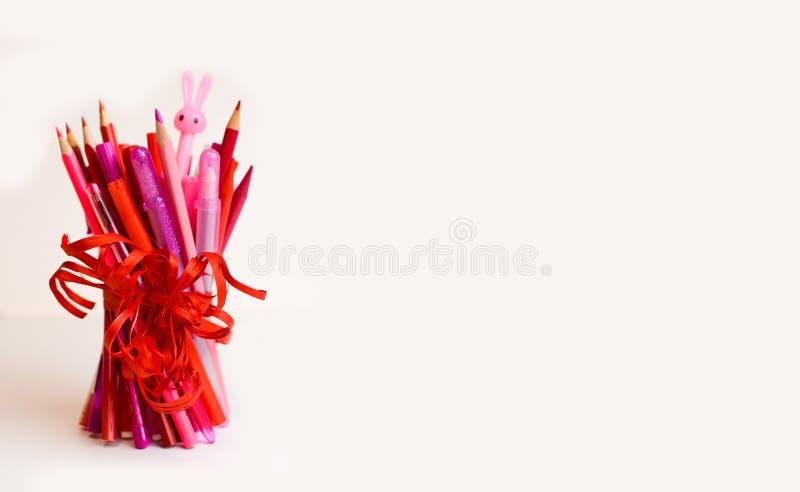 Um grupo de lápis apontados, de canetas com ponta de feltro em vermelho e em cor-de-rosa, e de uma pena na forma de um coelho fotografia de stock royalty free