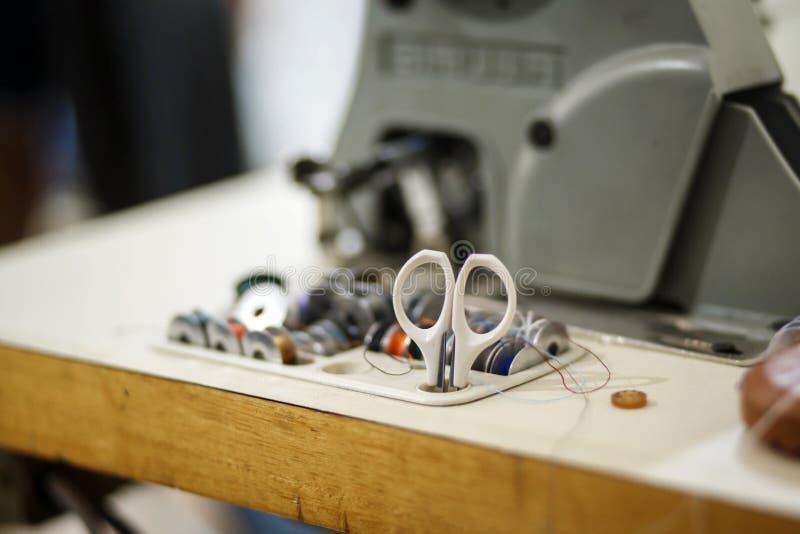 Um grupo de linha colorida para uma máquina de costura e umas tesouras brancas Costureira do local de trabalho Costurando a indús imagem de stock royalty free
