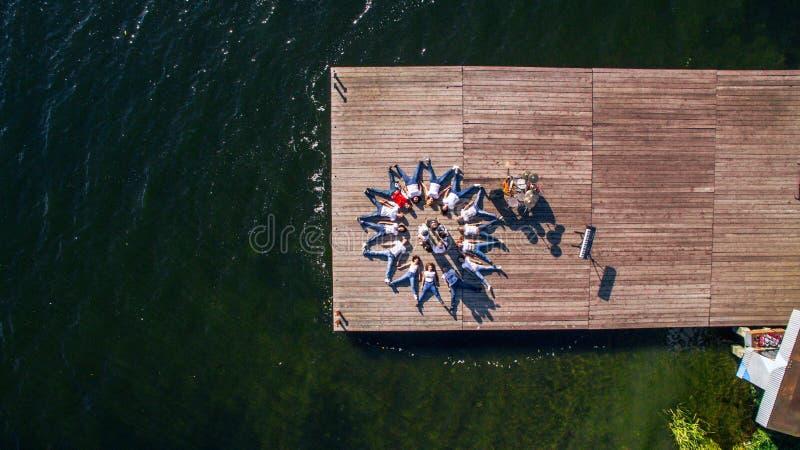 Um grupo de músicos e os cantores encontram-se no cais no rio surrealism Vista de acima Silhueta do homem de negócio Cowering imagem de stock royalty free
