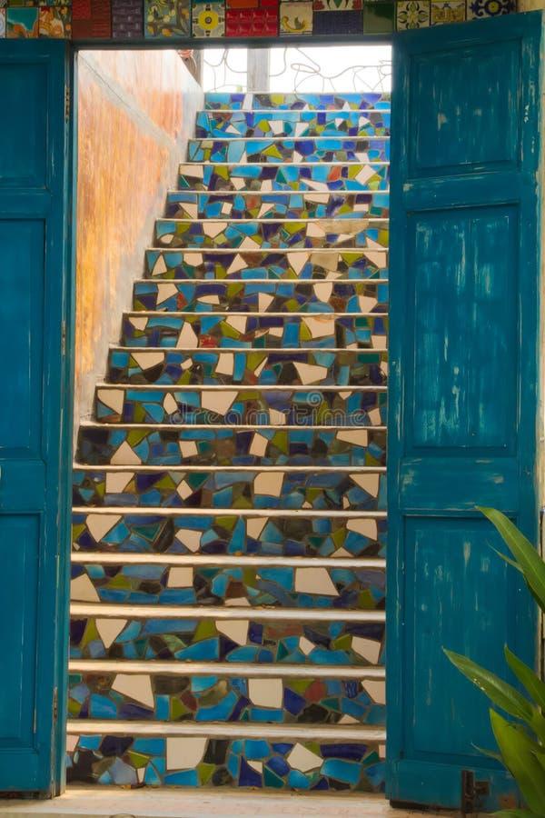 Um grupo de madeira azul rústico bonito de portas, conduzindo a uma escadaria telhada bonita, em um restaurante muito criativo do imagens de stock