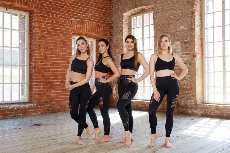 Um grupo de meninas desportivas novas que estão no salão para dançar Companheiros fêmeas no gym, relaxando após a aptidão imagem de stock