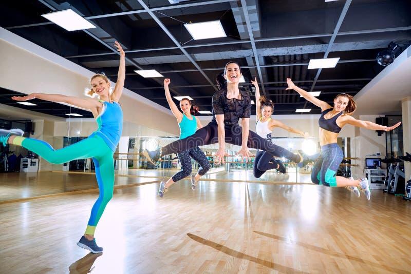 Um grupo de meninas salta com sorrisos no gym fotos de stock