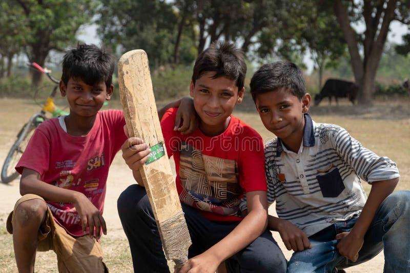 Um grupo de meninos levanta para uma foto ao jogar o grilo fora de Bhadarsa fotografia de stock