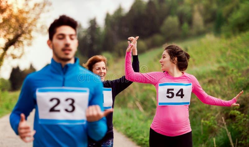 Um grupo de multi povos da geração que correm uma competição da raça na natureza foto de stock