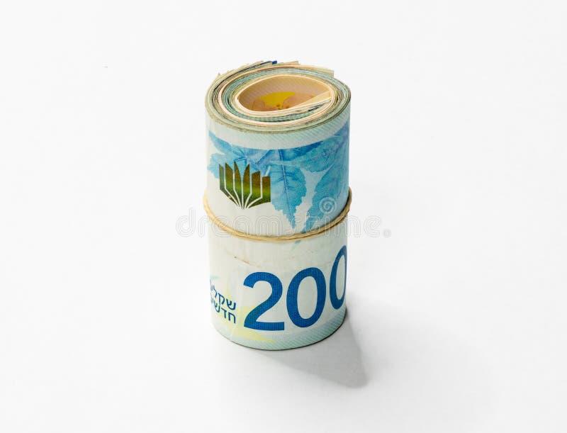 Um grupo de notas novas israelitas do dinheiro do NIS dos shekels rolou acima e mantido unido com um elástico simples em um backg fotografia de stock royalty free