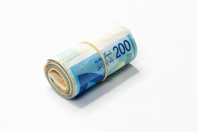 Um grupo de notas novas israelitas do dinheiro do NIS dos shekels rolou acima e mantido unido com um elástico simples em um backg fotografia de stock