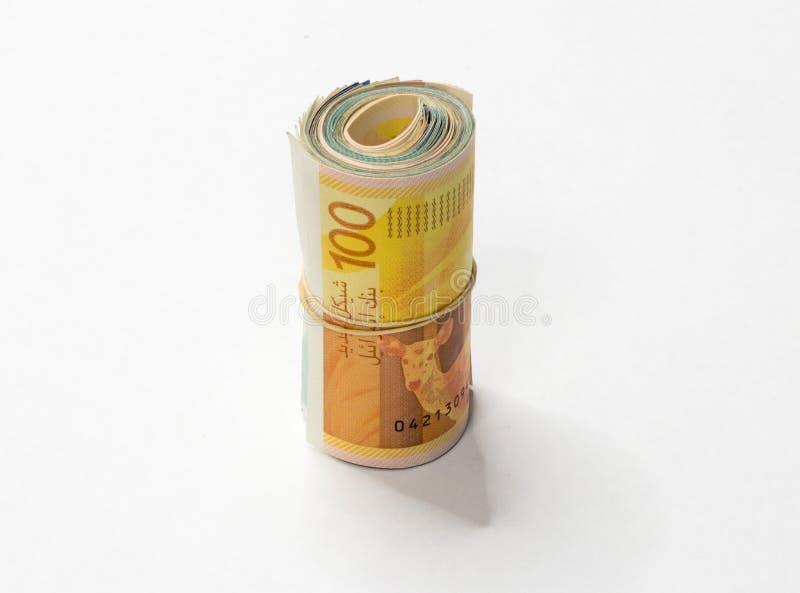 Um grupo de notas novas israelitas do dinheiro do NIS dos shekels rolou acima e mantido unido com um elástico simples em um backg fotos de stock royalty free