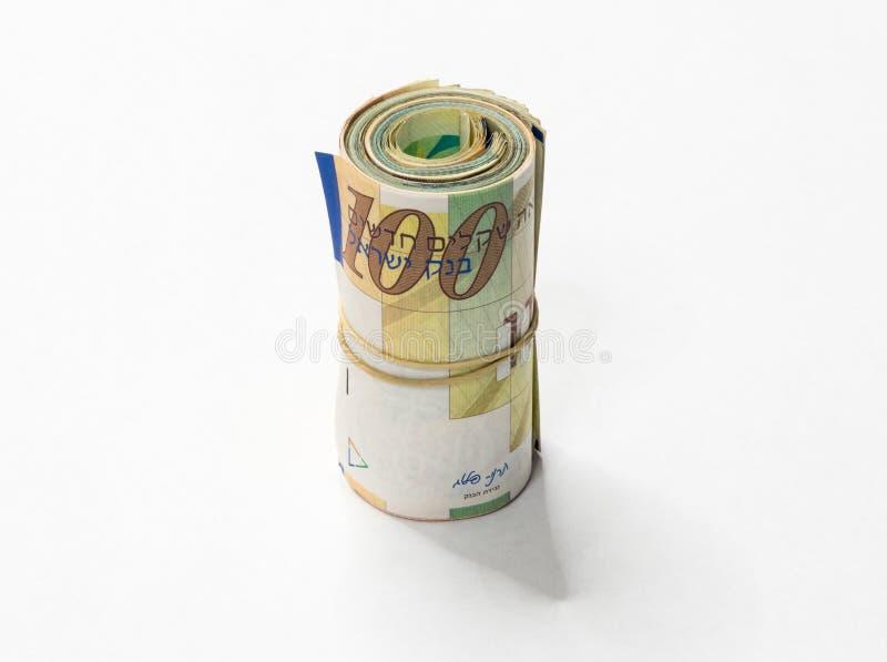 Um grupo de notas novas israelitas do dinheiro do NIS dos shekels rolou acima e mantido unido com um elástico simples em um backg foto de stock