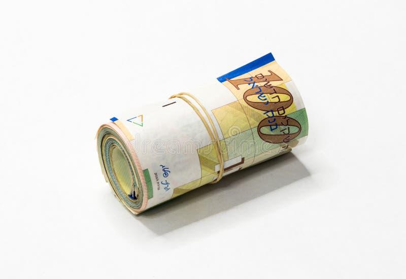 Um grupo de notas novas israelitas do dinheiro do NIS dos shekels rolou acima e mantido unido com um elástico simples em um backg fotos de stock