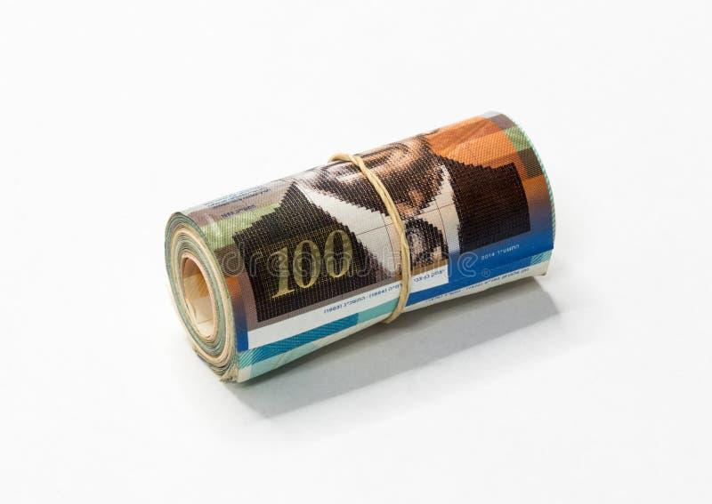 Um grupo de notas novas israelitas do dinheiro do NIS dos shekels rolou acima e mantido unido com um elástico simples em um backg imagens de stock royalty free