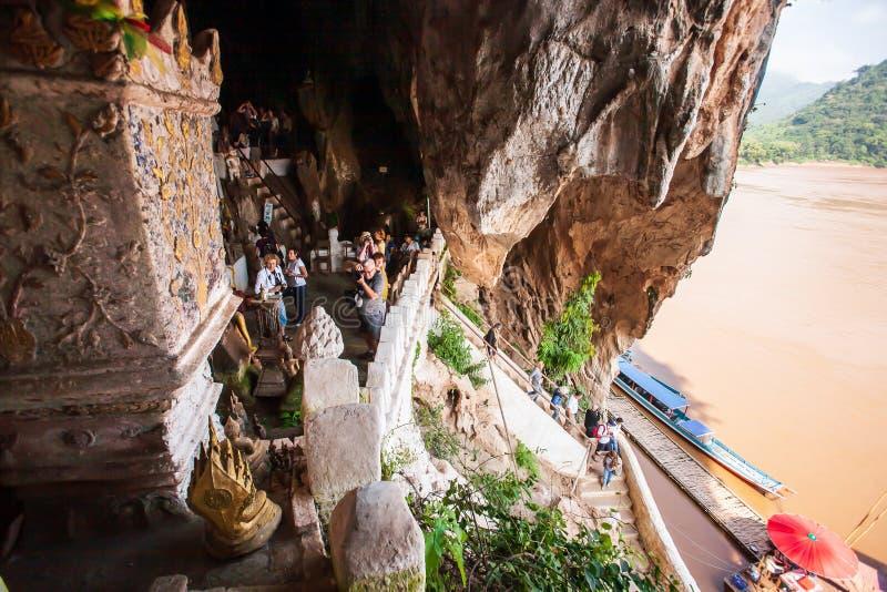 Um grupo de opinião impressionante dos turistas e de foto da tomada em Pak Ou Caves, cavernas famosas no penhasco da pedra calcár fotografia de stock royalty free