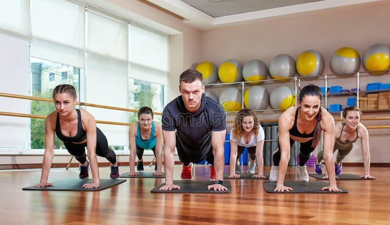 Um grupo de ostentar jovens no sportswear, em uma sala da aptidão, fazendo impulso-UPS ou pranchas no gym Aptid?o do grupo imagens de stock royalty free