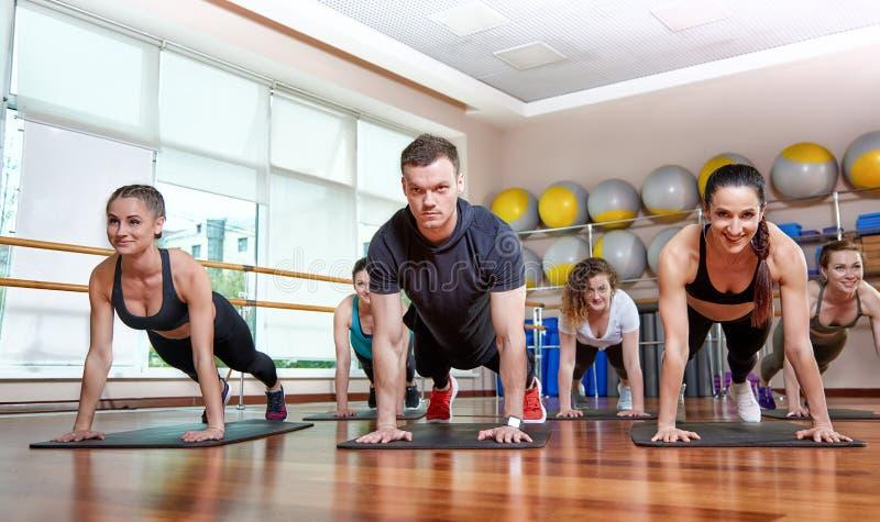 Um grupo de ostentar jovens no sportswear, em uma sala da aptidão, fazendo impulso-UPS ou pranchas no gym Aptid?o do grupo imagem de stock