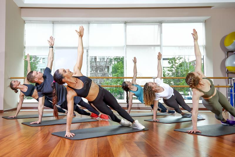 Um grupo de ostentar jovens no sportswear, em uma sala da aptidão, fazendo impulso-UPS ou pranchas no gym Aptid?o do grupo fotografia de stock