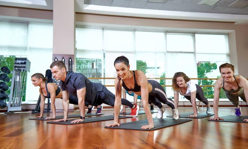 Um grupo de ostentar jovens no sportswear, em uma sala da aptidão, fazendo impulso-UPS ou pranchas no gym Aptid?o do grupo fotos de stock