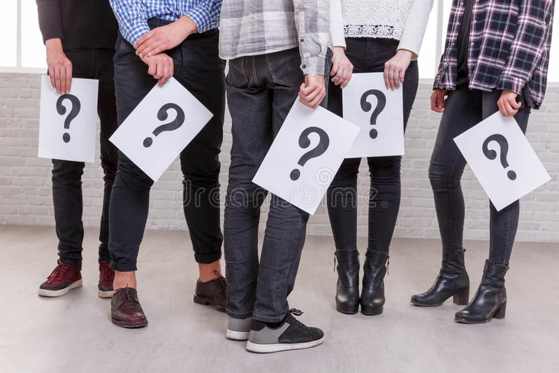 Um grupo de pessoas é mostrado incompletamente com suas mãos para baixo em qual as folhas com o ponto de interrogação imagens de stock