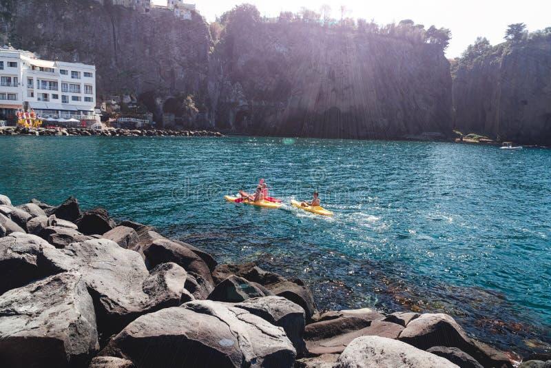 Um grupo de pessoas em caiaque está navegando Itália, Sorrento, baía do meta é destino popular do turista para o esporte que kaya fotografia de stock