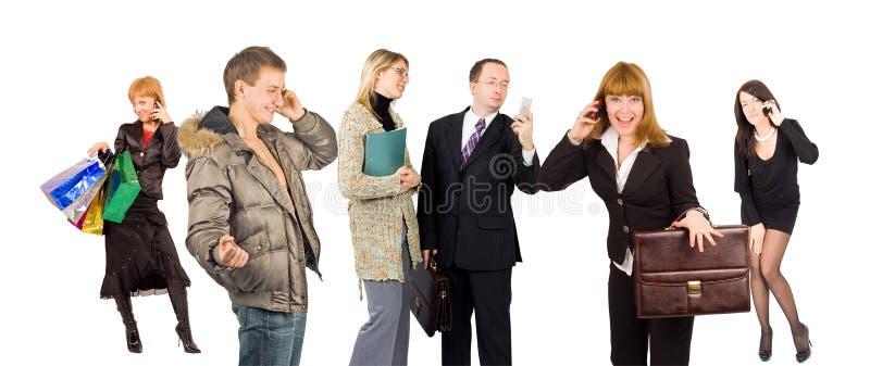 Um grupo de pessoas envolvido na fala do telefone fotos de stock