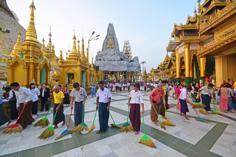 Um grupo de pessoas que ajuda a varrer o assoalho no pagode de Shwedagon imagens de stock royalty free