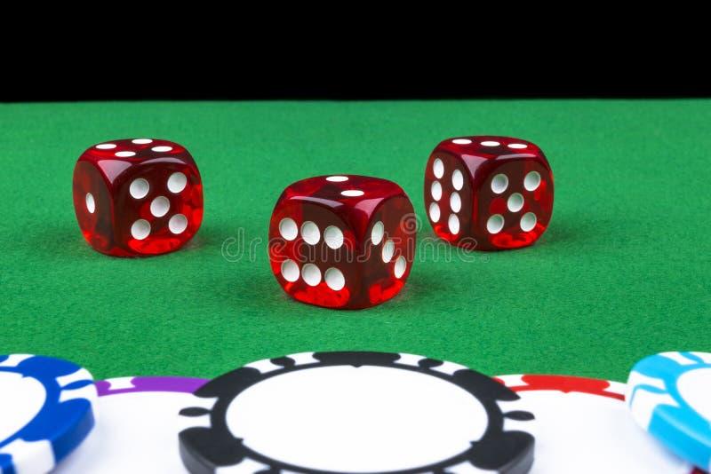 Um grupo de pilha das microplaquetas de pôquer em uma tabela de jogo verde com um dado rola Fundo preto conceito do risco - jogan foto de stock royalty free