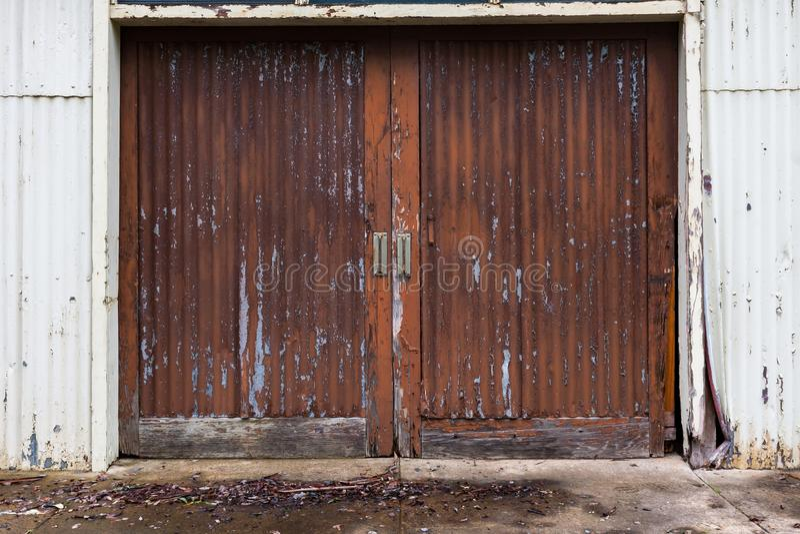 Um grupo de portas de celeiro resistidas da vertente com pintura desvanecida como um abstra fotografia de stock