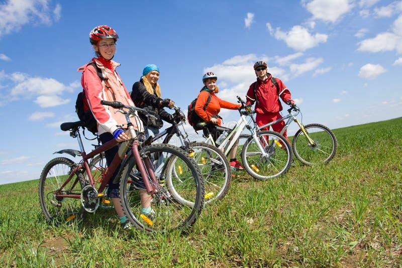 Um grupo de quatro adultos em bicicletas. fotos de stock royalty free