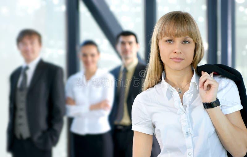 Um grupo de quatro pessoas do negócio em um escritório imagem de stock