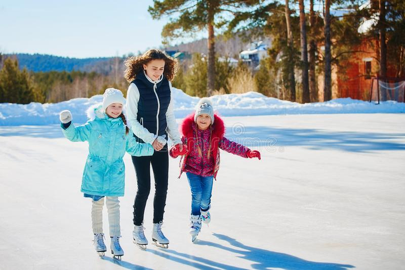 Um grupo de três meninas em uma pista de patinagem do inverno Rolo e riso imagens de stock royalty free