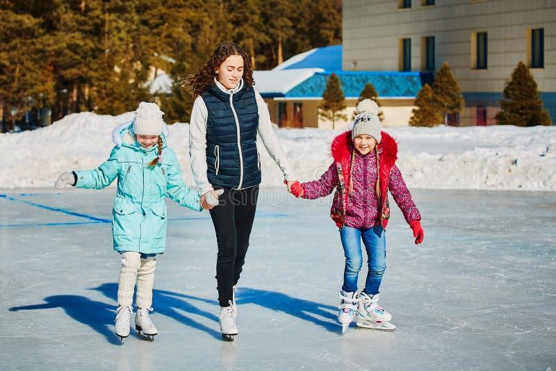 Um grupo de três meninas em uma pista de patinagem do inverno Rolo e riso Pista de patinagem na natureza imagens de stock royalty free