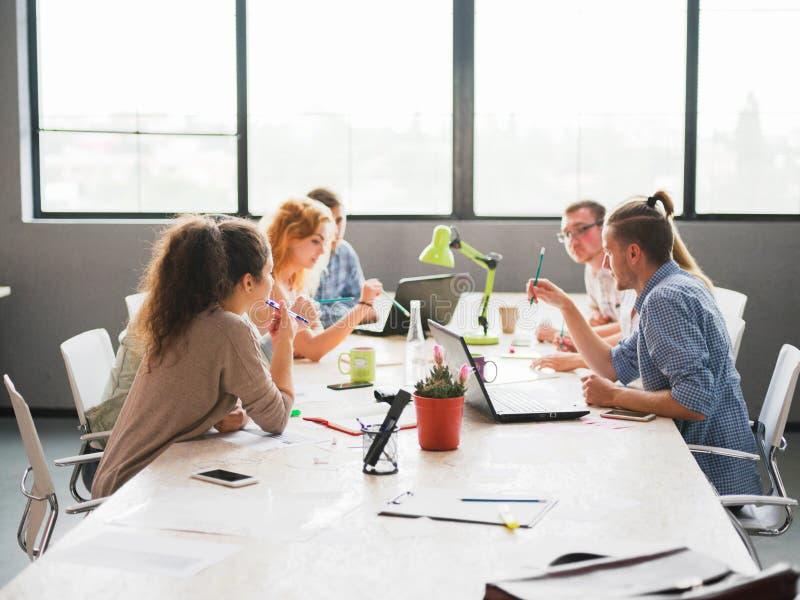 Um grupo de trabalhadores de escritório que discutem os problemas de negócio do ` s da empresa foto de stock