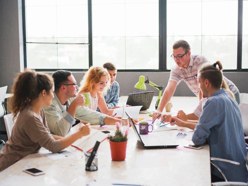 Um grupo de trabalhadores de escritório que discutem os problemas de negócio do ` s da empresa fotos de stock