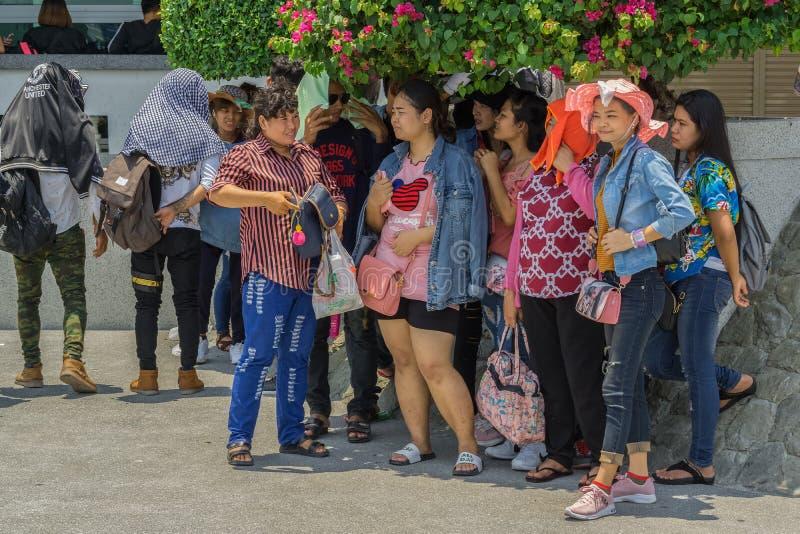 Um grupo de turistas chineses está escondendo do sol abaixo de uma árvore pequena imagens de stock royalty free
