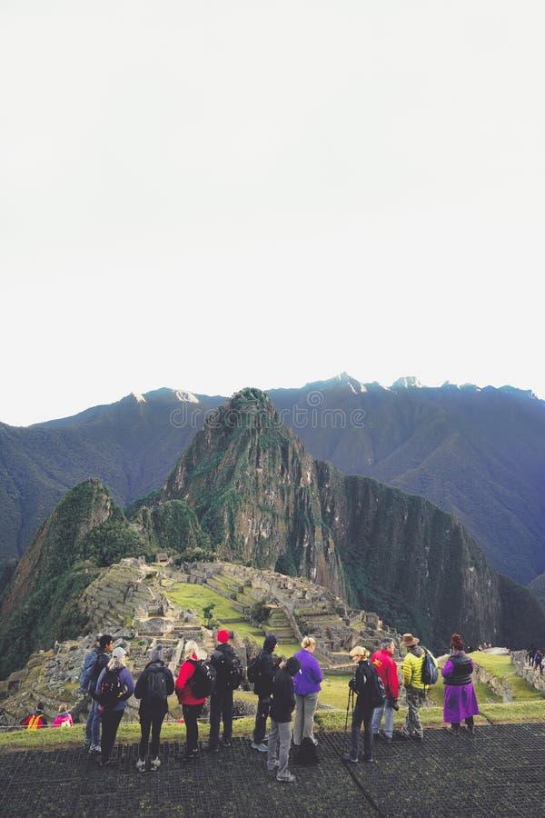 Um grupo de turistas está olhando a cidade perdida dos Incas e está tomando fotos no primeiro plano imagem de stock royalty free