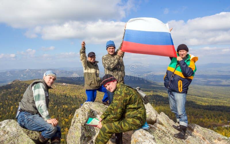 Um grupo de turistas na parte superior da montanha Yalangas nos Ural do sul com a bandeira nacional do russo imagens de stock