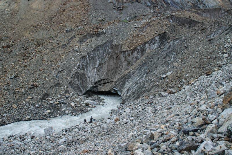 Um grupo de turistas vai ao longo de um rio frio da montanha de uma geleira na montagem Ushba na região de Svaneti imagem de stock