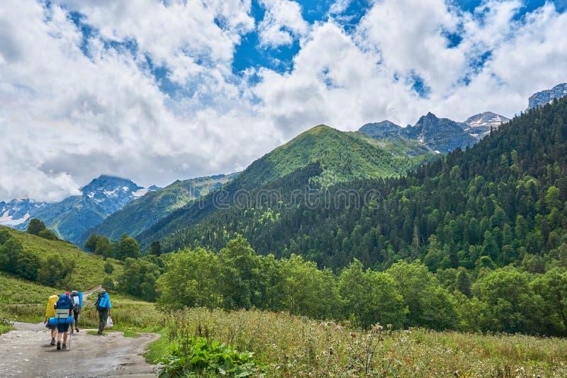 Um grupo de turistas vai em uma rota nas montanhas imagem de stock