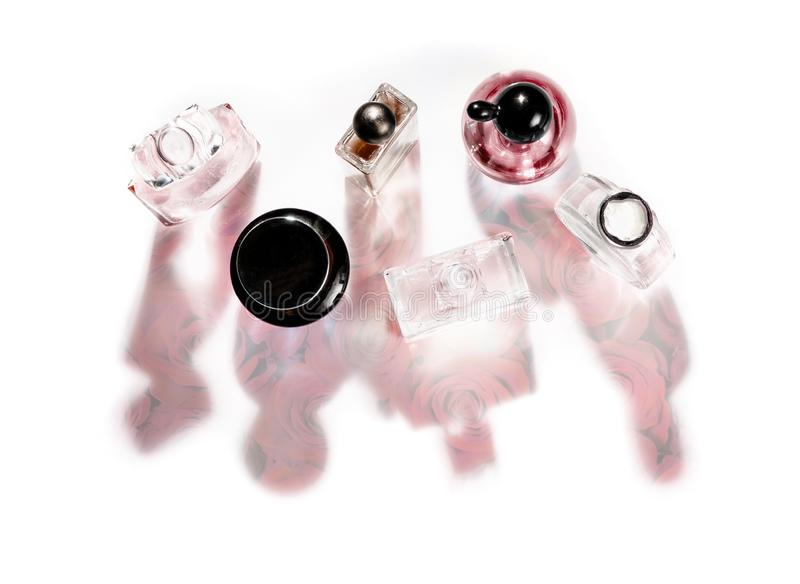 Um grupo de várias garrafas de perfume cor-de-rosa com uma flor cor-de-rosa nas sombras Identificação na parte superior fotos de stock royalty free
