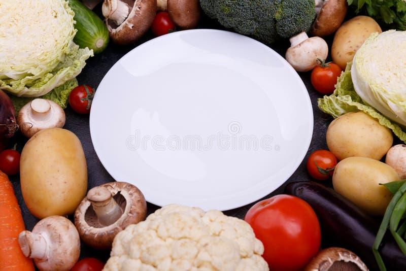 Um grupo de vegetais em torno da placa foto de stock
