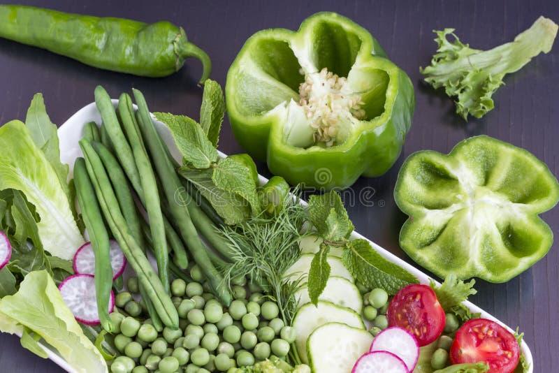 Um grupo de vegetais: ervilhas, pimenta verde, rabanetes, pepino Fundo preto imagens de stock