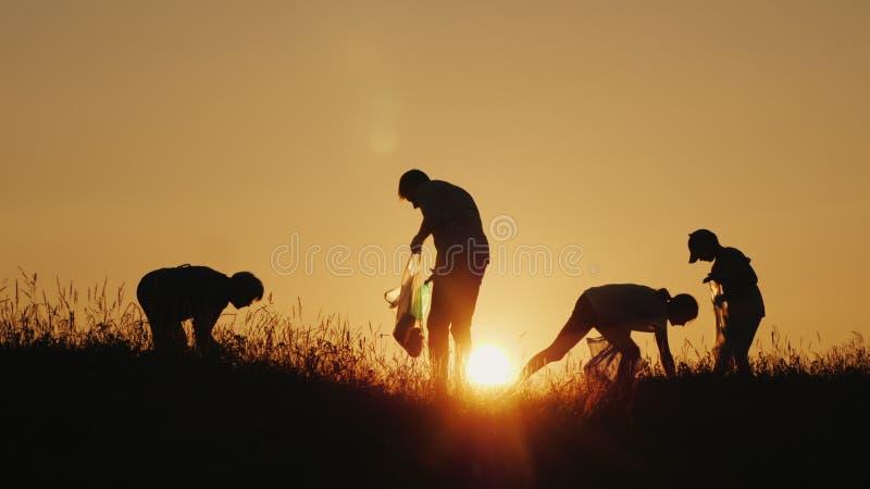 Um grupo de voluntários pegara o lixo na natureza Limpe o conceito do ambiente fotografia de stock
