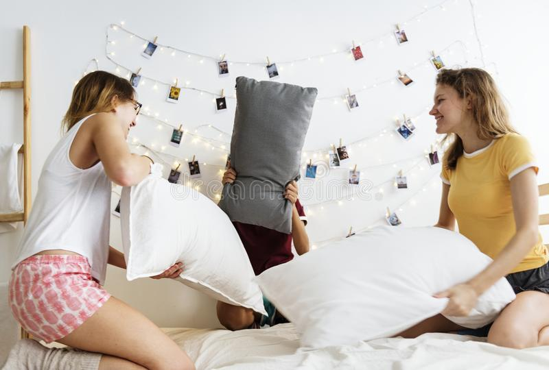 Um grupo diverso de mulheres que jogam a luta de descanso na cama junto foto de stock