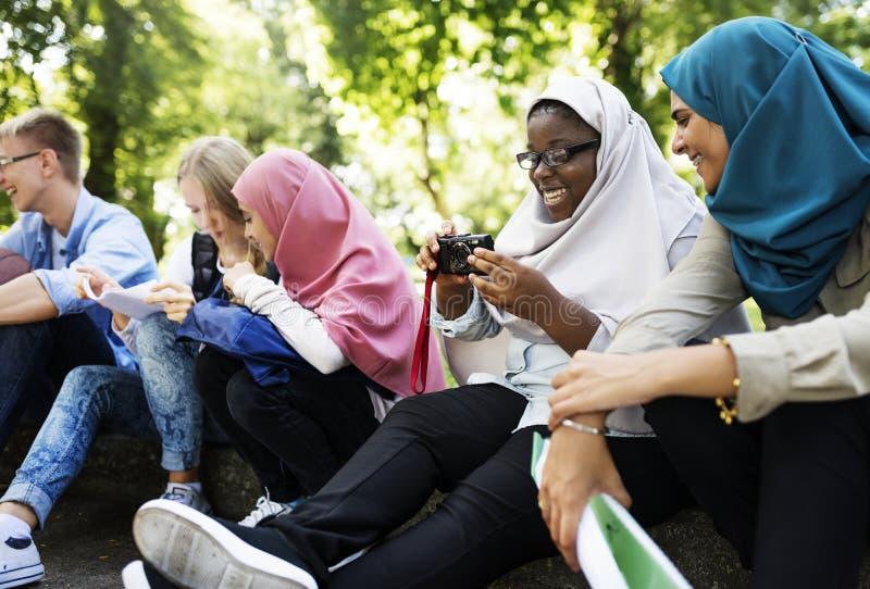 Um grupo diverso do adolescente pendura para fora no parque foto de stock