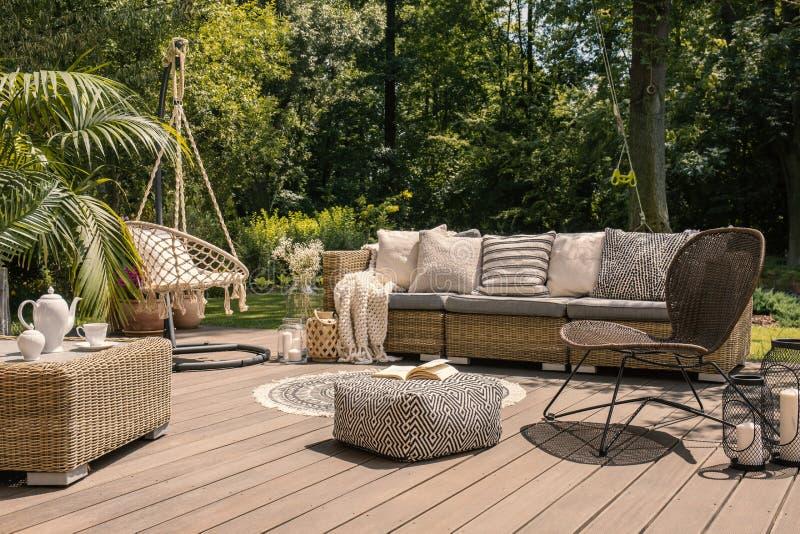 Um grupo do pátio do rattan que inclui um sofá, uma tabela e uma cadeira em um wo imagens de stock royalty free