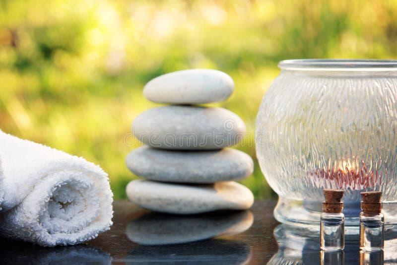 Um grupo do tratamento dos termas, as pedras da massagem, uma toalha e o óleo da massagem são colocados em uma tabela lustrada do imagem de stock royalty free