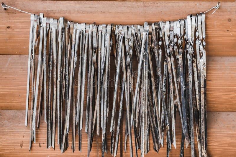 Um grupo grande de espetos velhos do metal para a carne está em um fio em dois pregos em um fundo alaranjado da parede das placas foto de stock