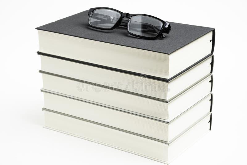 Um grupo ordenadamente empilhado de cinco livros com vidros de leitura imagens de stock
