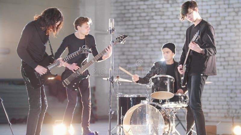 Um grupo rock novo que tem uma repetição em uma garagem Membros de um grupo que veste a roupa preta Iluminação brilhante foto de stock