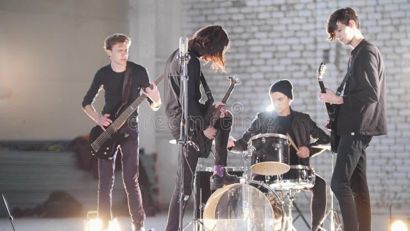Um grupo rock novo que tem uma repetição em um hangar Membros de um grupo que veste a roupa preta Iluminação brilhante imagem de stock royalty free